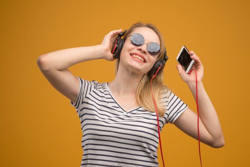 Een vrolijk hipstermeisje die aan muziek op hoofdtelefoons met een telefoon op een gele achtergrond luisteren royalty-vrije stock foto's