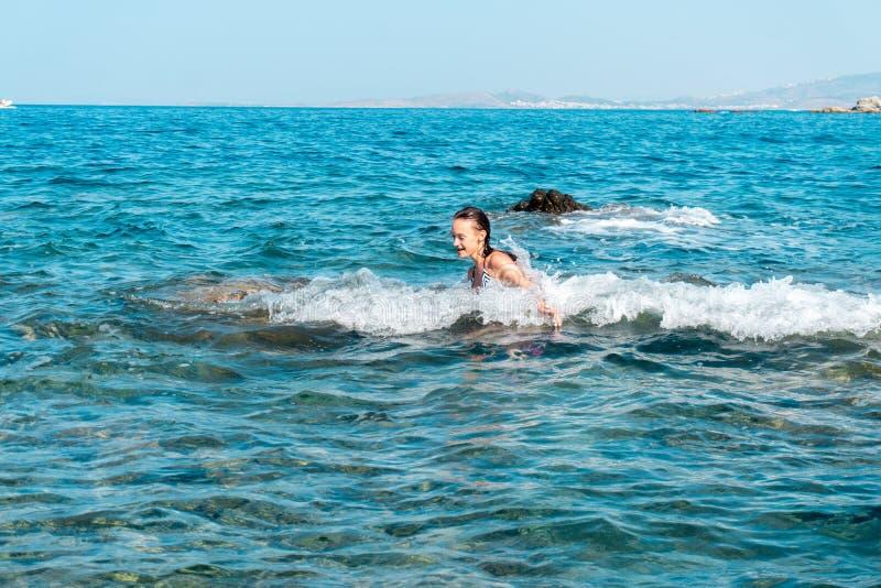 Een vrolijk jong meisje zwemt in het overzees royalty-vrije stock afbeeldingen