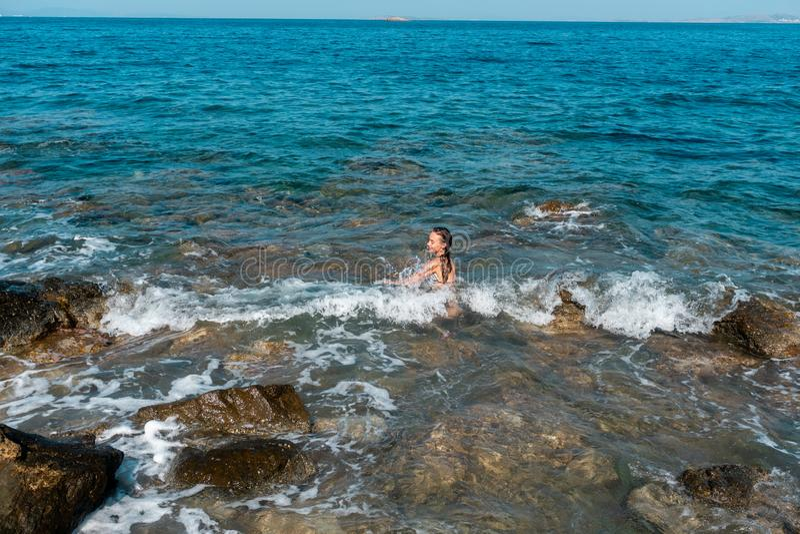 Een vrolijk jong meisje zwemt in het overzees stock afbeelding
