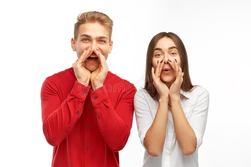 Een vrolijk jong paar een man en een vrouw hun zetten dient een mondstuk voor hun gezichten in en geschreeuwd in steun stock foto