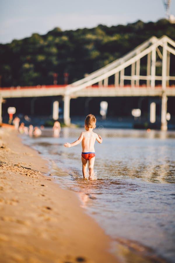 Een vrolijk mannelijk kind van drie jaar die langs het strand dichtbij het water en de bespattende vlieg lopen Actieve Recreatie  royalty-vrije stock afbeelding