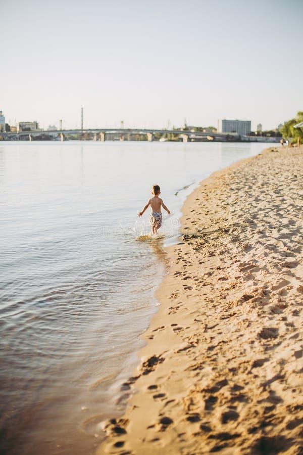 Een vrolijk mannelijk kind van drie jaar die langs het strand dichtbij het water en de bespattende vlieg lopen Actieve Recreatie  stock afbeelding