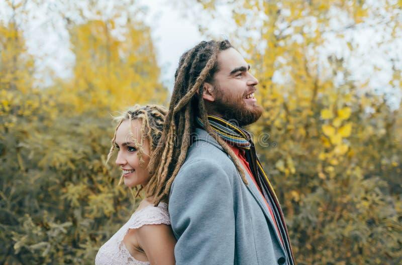 Een vrolijk paar bevindt zich rijtjes Bruid en bruidegom met dreadlocks die pret op aard hebben De ceremonie van het huwelijk in  stock foto