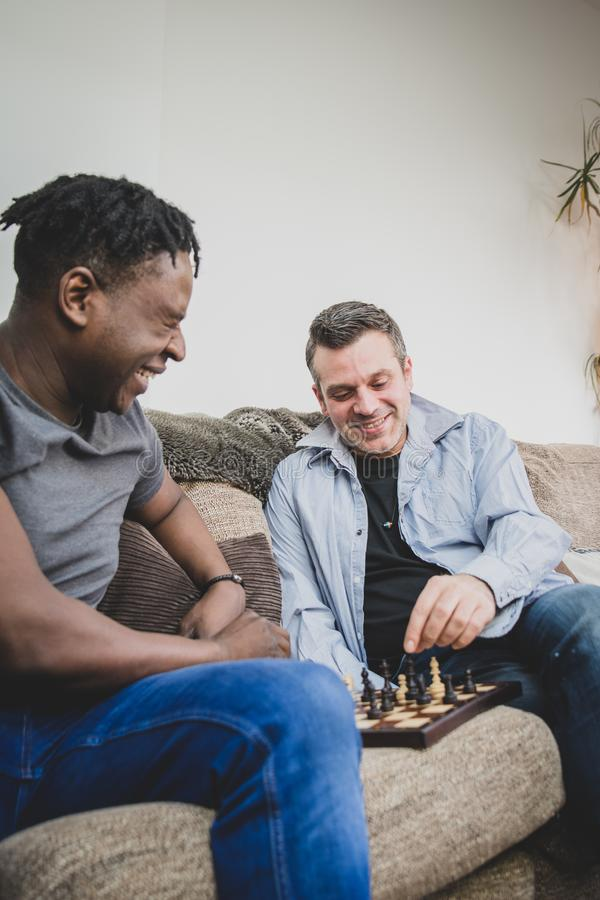 Een vrolijk paar die van tijd genieten die binnen thuis, schaak spelen stock foto