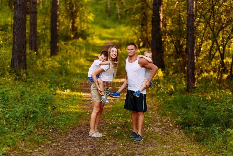 Een vrolijke jonge man en een vrouw houden in openlucht twee kinderen op hun ruggen in de zomer Familie royalty-vrije stock fotografie