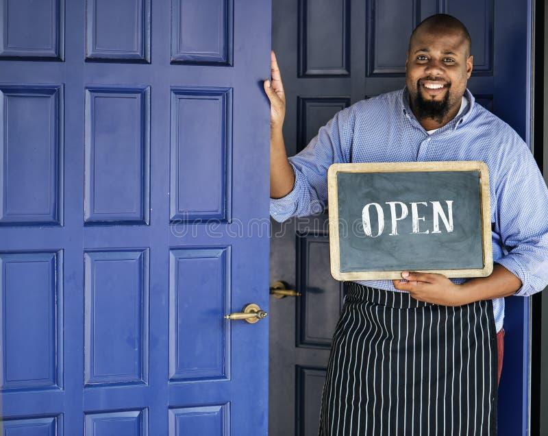 Een vrolijke kleine bedrijfseigenaar met open teken stock foto
