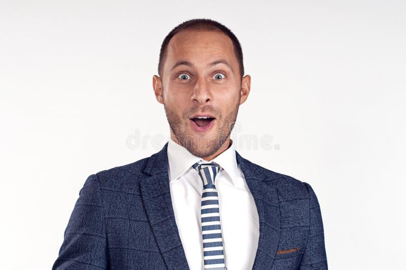 Een vrolijke mens in een kostuum met een band is verrast Witte achtergrond Geïsoleerd beeld royalty-vrije stock foto
