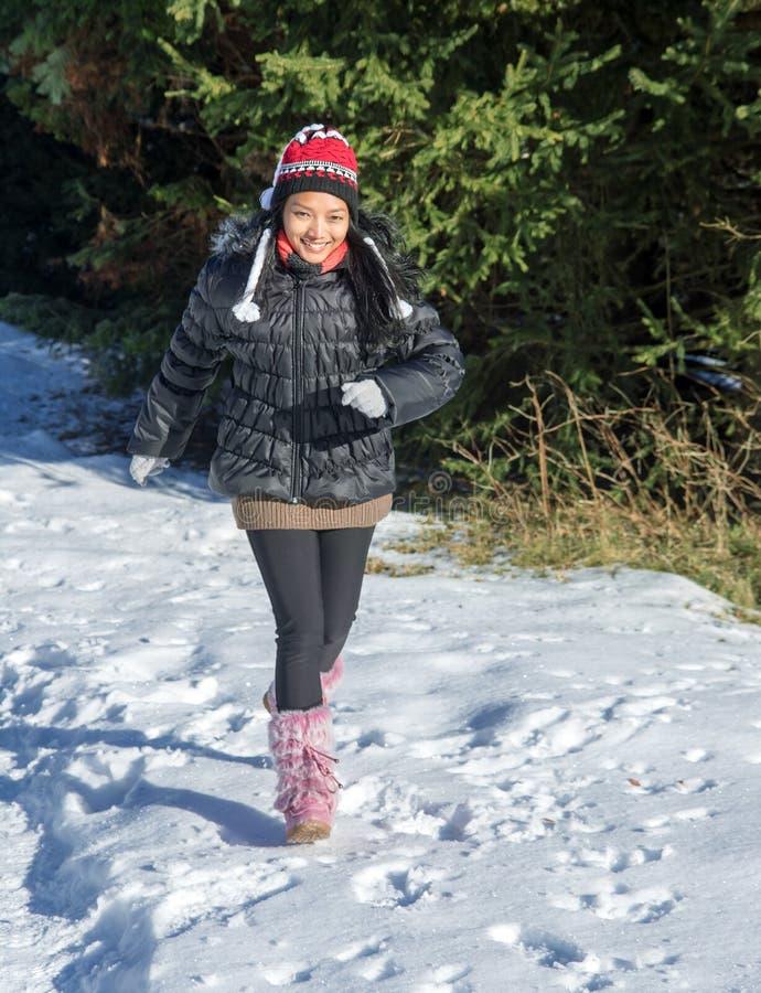 Een vrolijke vrouw die in een sneeuwaard lopen royalty-vrije stock afbeelding