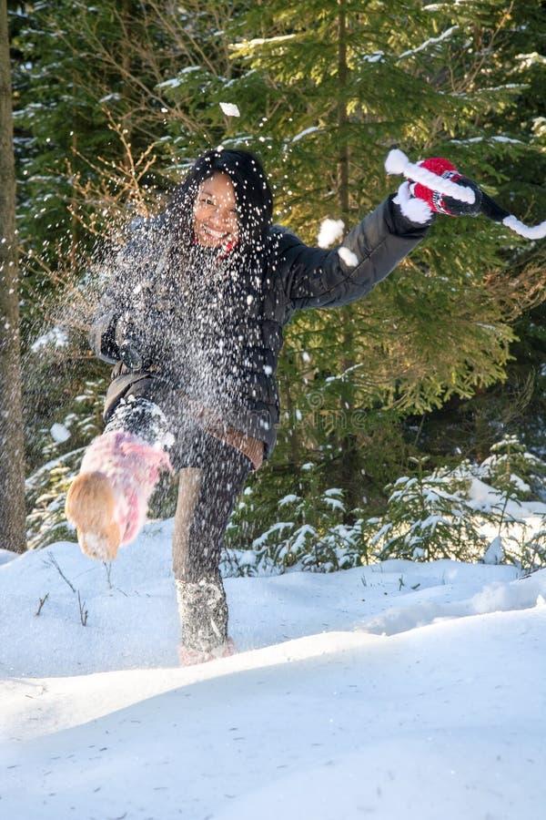 Een vrolijke vrouw schopt sneeuw royalty-vrije stock foto's