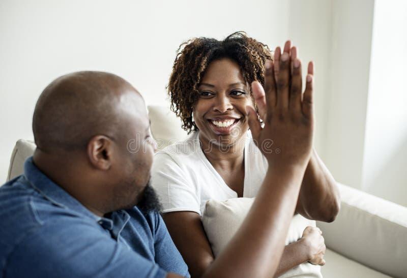 Een vrolijke zwarte paar toetredende handen stock foto's