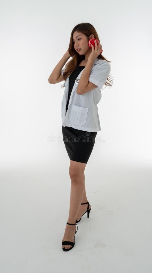 Een vrouw arts die stelt het dragen van een rode hoofdtelefoon met een sthethoscope op haar hals bevinden zich stock fotografie