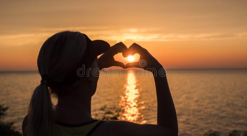 Een vrouw bekijkt het overzees waar de zonreeksen, een hart-vormig cijfer toont royalty-vrije stock afbeeldingen