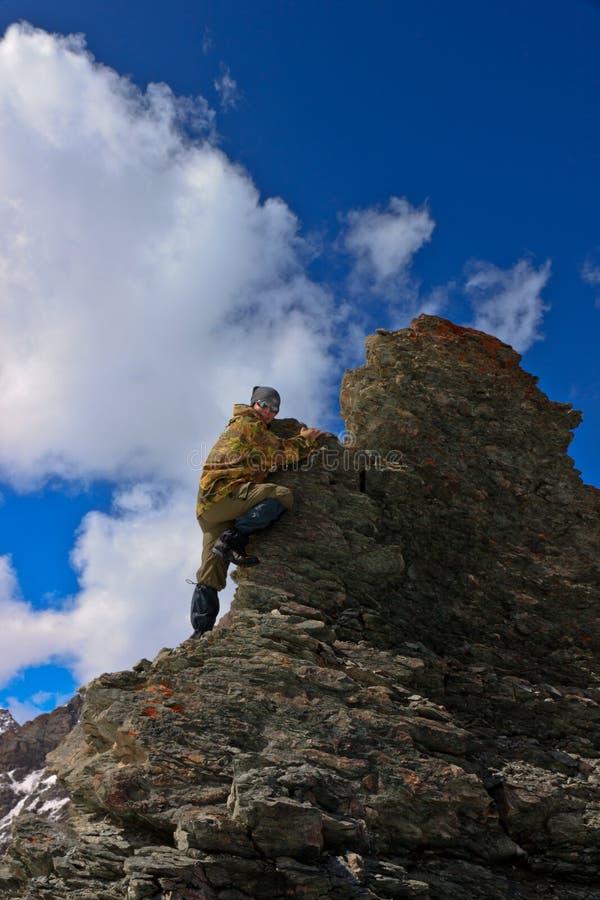 Een vrouw beklimt een klip. stock afbeelding