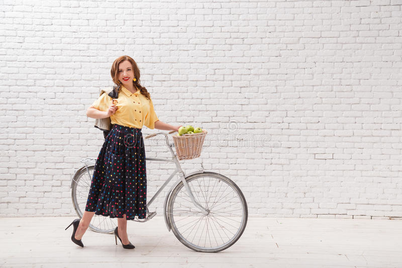 Een vrouw berijdt een fiets met een gewas van appelen in een mand stock fotografie