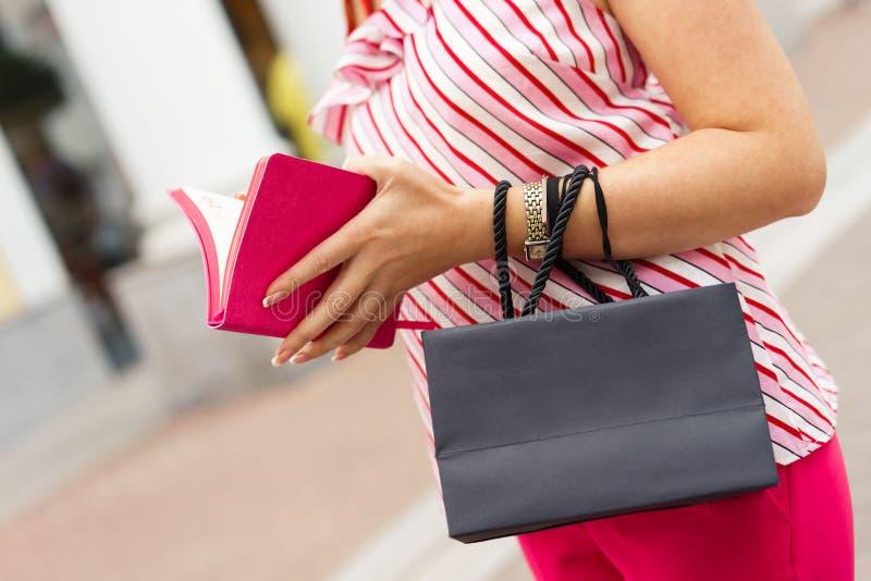 Een vrouw bevindt zich met een zwarte document zak in haar handen Het winkelen concept Ruimte voor tekst op de zak stock foto's