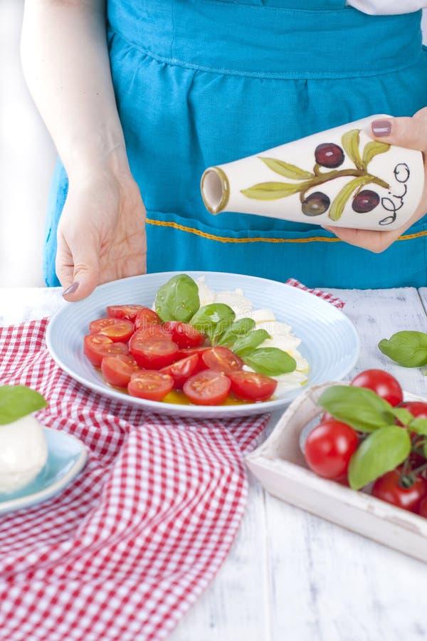 Een vrouw in een blauwe schort bereidt een traditionele Italiaanse salade met kersentomaten en tomaten voor, die het kruiden met  stock fotografie