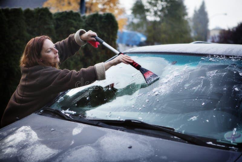 Een vrouw buiten het afdanken van vorst van haar windscherm in de winter stock afbeeldingen