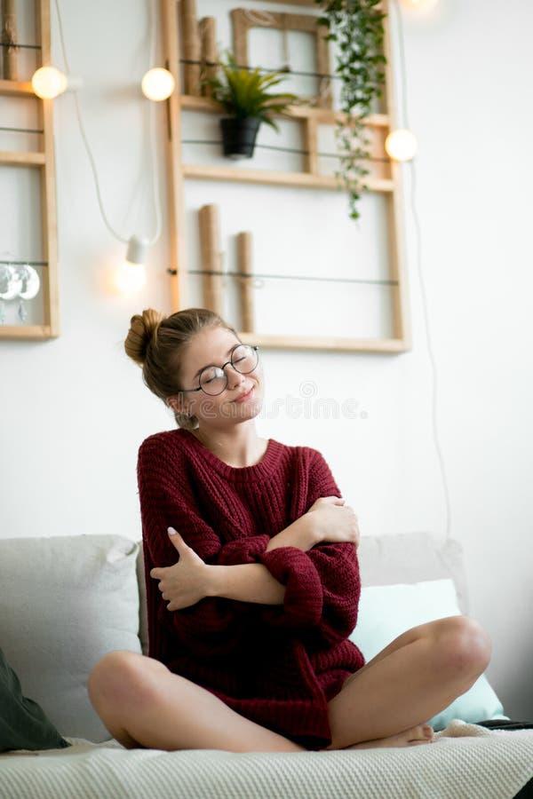 Een vrouw in comfortabele sweater koestert zich aangezien van zij wil worden gehouden stock afbeeldingen