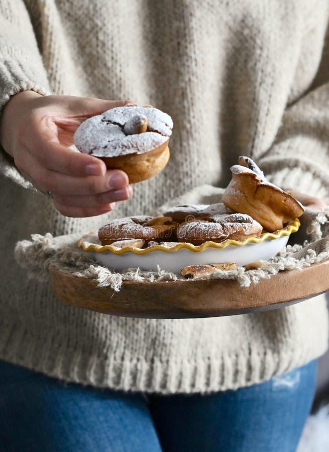 Een vrouw in de muffins van een sweaterholding met suikerglazuursuiker in haar handen Comfortabele foto in de stijl van het leven royalty-vrije stock foto