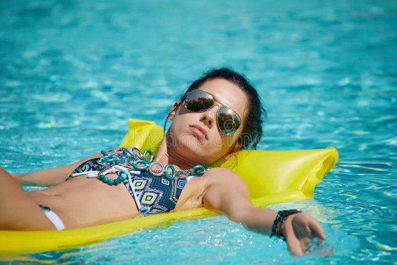 Een vrouw in de pool drijft op een opgeblazen matras royalty-vrije stock afbeeldingen