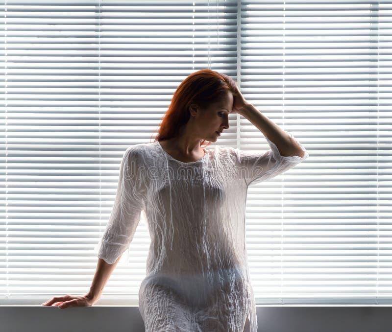 Een vrouw dichtbij het venster thuis royalty-vrije stock foto