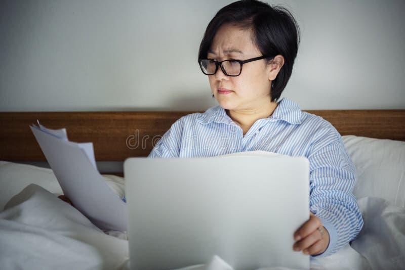 Een vrouw die aan laptop in bed werken stock afbeeldingen