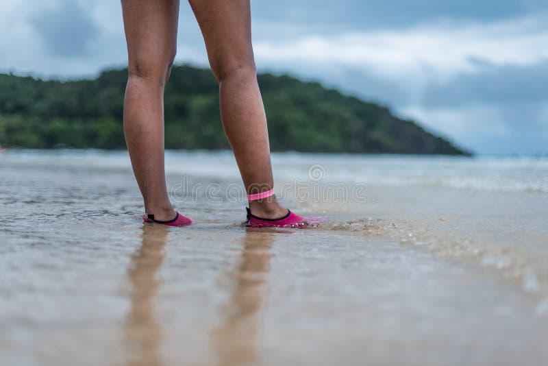 Een vrouw die in de ondiepte op het strand lopen royalty-vrije stock afbeelding
