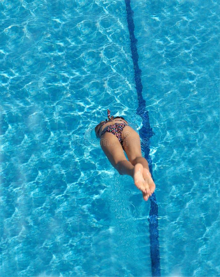 Een vrouw die in de pool springen een de zomerdag stock afbeelding