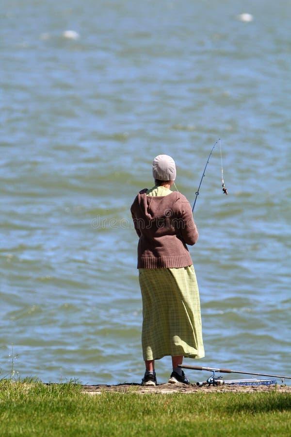 Een Vrouw die door het Meer vissen stock afbeeldingen