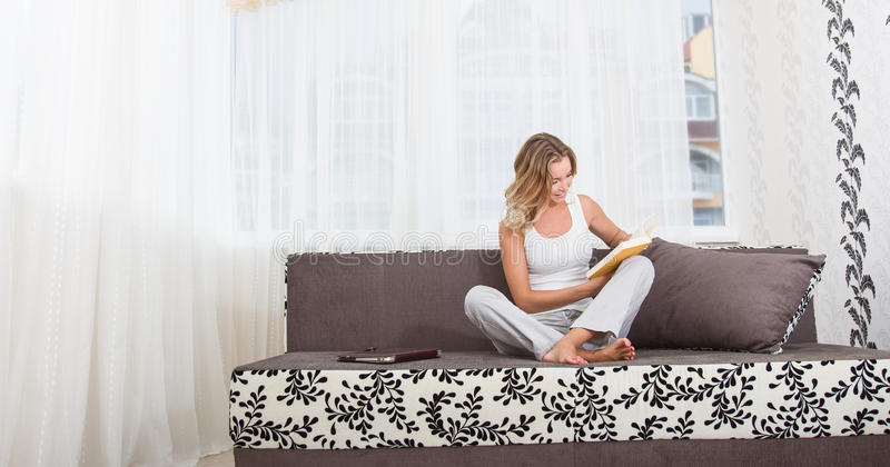 Een vrouw die een boek en het glimlachen lezen stock fotografie