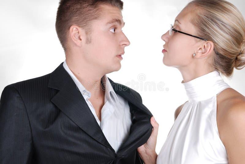 een vrouw die een halsboord van een man houdt stock afbeeldingen