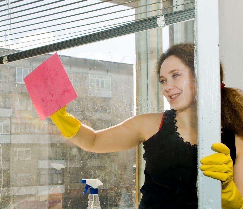 Een vrouw die een venster schoonmaakt royalty-vrije stock fotografie