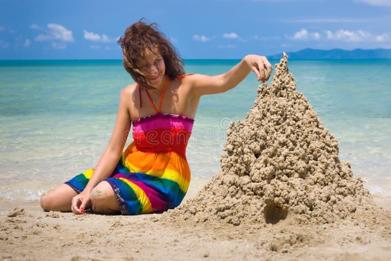 Een vrouw die een zandkasteel bouwt stock fotografie