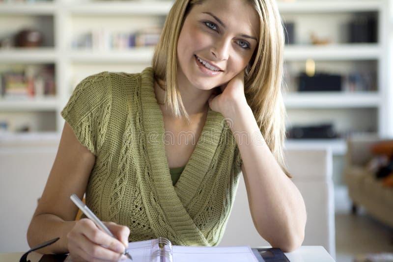 Een vrouw die in haar agenda schrijft stock afbeeldingen