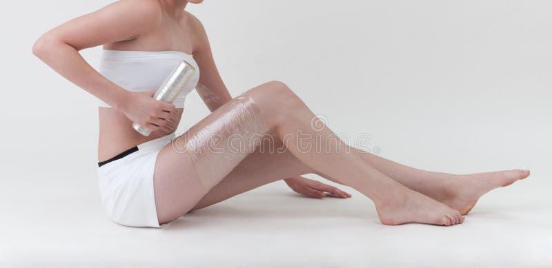 Een vrouw die haar been met plastic omslag verpakt royalty-vrije stock foto