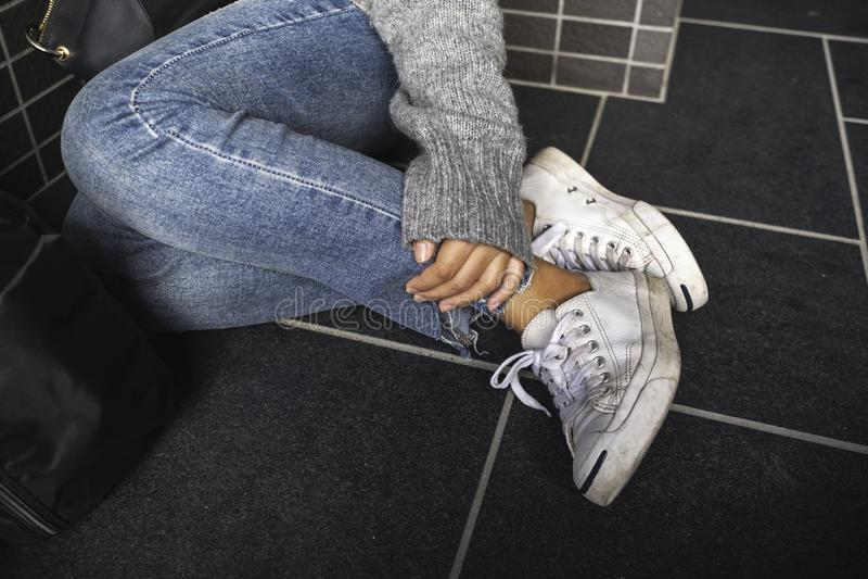 Een vrouw die Jean en witte tennisschoenen wat betreft haar been dragen terwijl het zitten op de vloer stock foto's