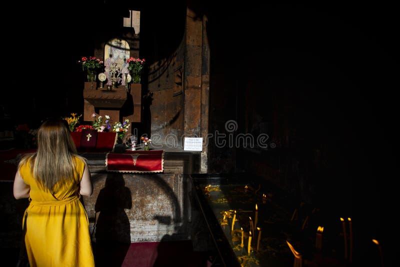 Een vrouw die in een kerk met kaarsen bidden, yerevan, Armenië royalty-vrije stock foto