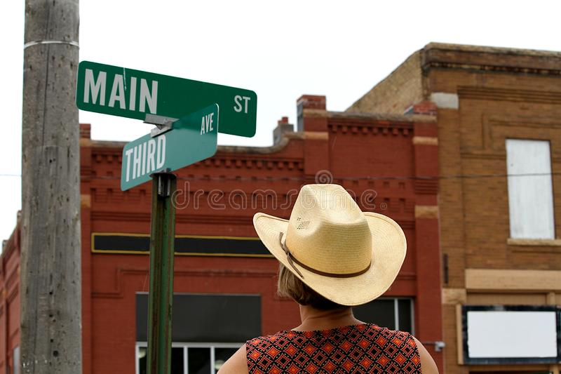 Een vrouw die een Main Street -teken in Amerika bekijken stock fotografie