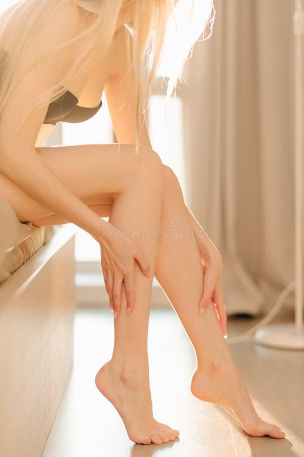 Een vrouw die in ondergoed met perfecte geschikte benen op bed in zonnige ruimte zitten royalty-vrije stock foto