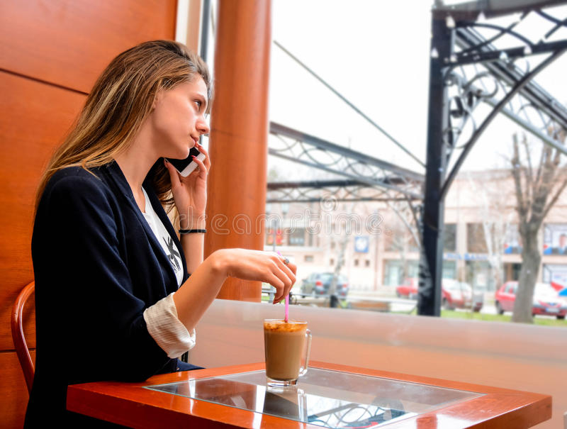 Een vrouw die op haar telefoon spreken en met een stro spelen dat in haar koffie is royalty-vrije stock afbeelding