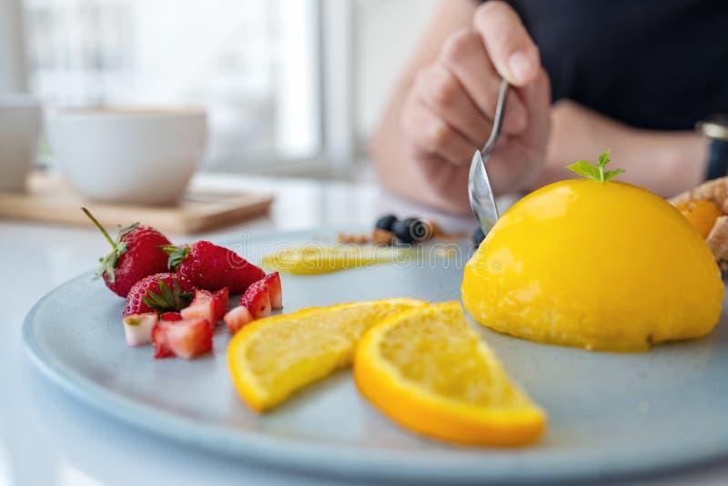 Een vrouw die oranje cake met gemengd fruit eten door lepel stock afbeelding