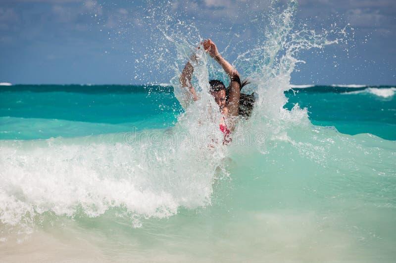 Een vrouw en een golf bespatten in het Caraïbische overzees stock afbeelding