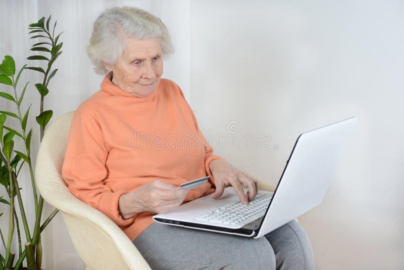 Een vrouw die van tachtig jaar aan laptop thuis werken royalty-vrije stock afbeelding