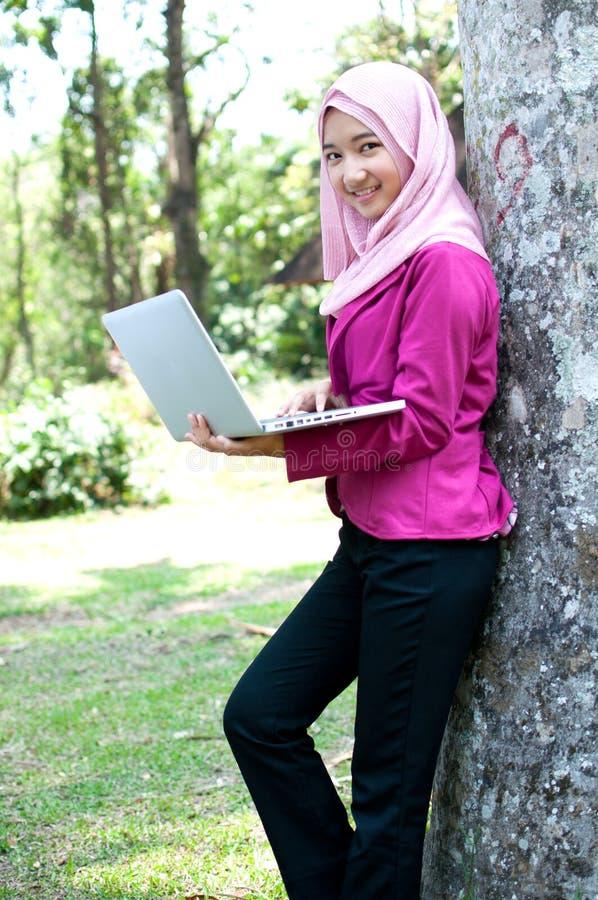 Een vrouw die zich met laptop bevinden royalty-vrije stock foto's