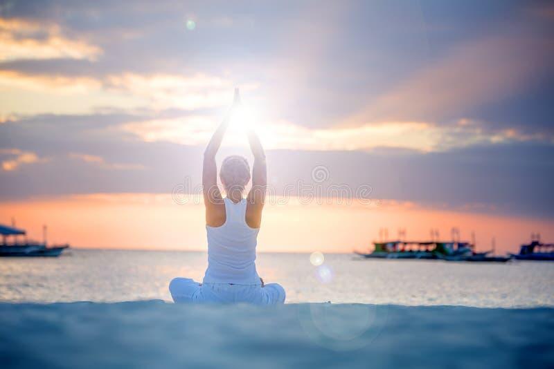 Een vrouw doet yogaoefeningen bij de zonsondergang op Boracay-eiland, royalty-vrije stock afbeelding