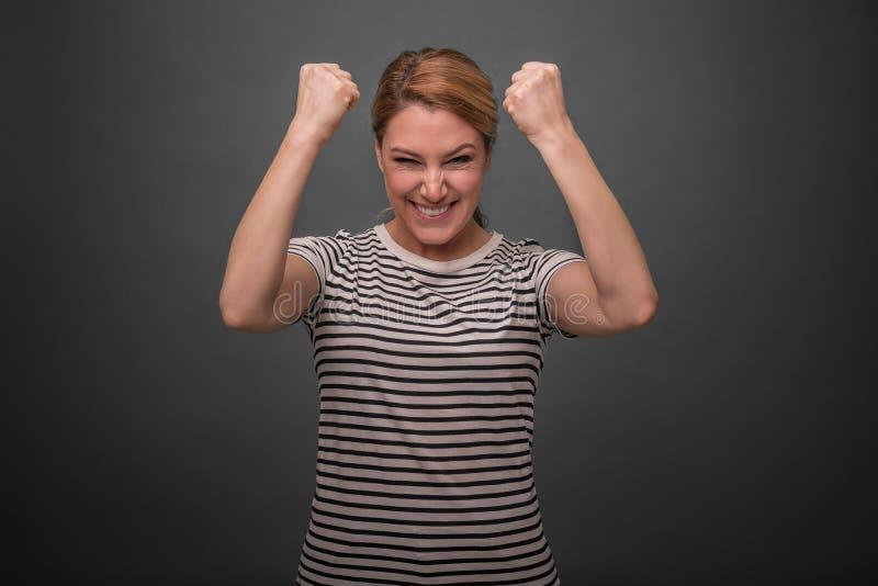 Een vrouw drukt emotioneel vreugde of succes op een grijze achtergrond uit royalty-vrije stock afbeelding