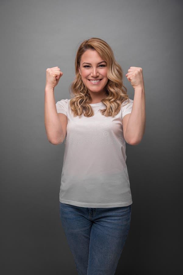 Een vrouw drukt emotioneel vreugde of succes op een grijze achtergrond uit stock foto's
