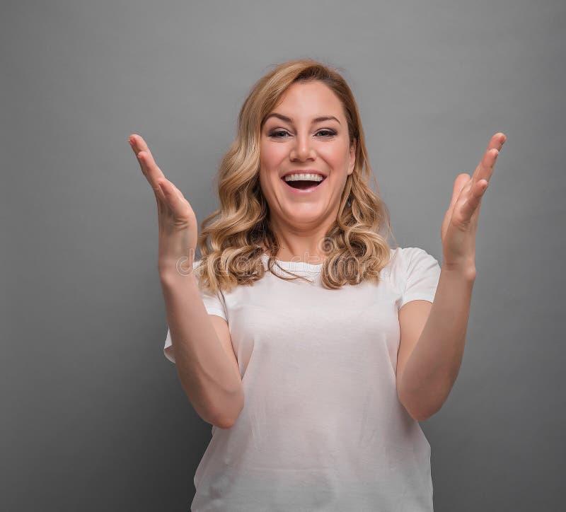 Een vrouw drukt emotioneel vreugde of succes op een grijze achtergrond uit royalty-vrije stock foto