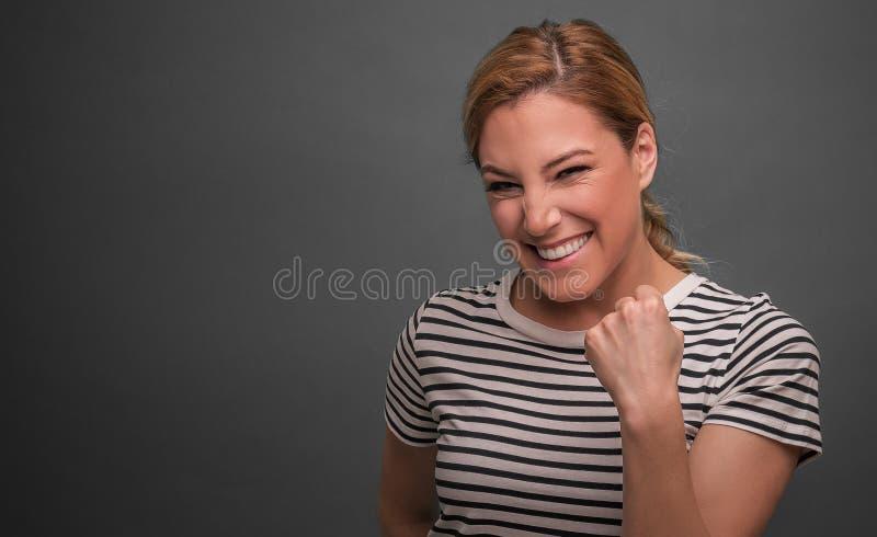 Een vrouw drukt emotioneel vreugde of succes op een grijze achtergrond uit stock afbeelding