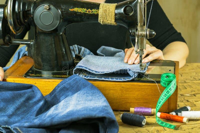 Een vrouw in een zwarte col naaiende jeans stock foto